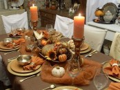 a vintage Thanksgiving tablescape done in brown and rust, with metal chargers, metallic and neutral pumpkins, pinecones, rust candles in candleholders, shiny gold plates and cutlery
