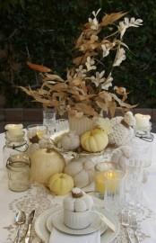 a vintage rustic Thanksgiving tablescape with a lace runner, white textiles, a dried leaf and flower centerpiece, white and neutral pumpkins, candles in glasses and white porcelain is a chic one