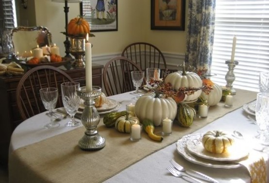 a neutral Thanksgiving tablescape with neutral linens, white porcelain, faux and nautral pumpkins, silver candleholders and candles