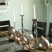 a burlap runner, silver buckets and candleholders, white candles, white and silver pumpkins for a refined vintage Thanksgiving tablescape