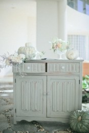 a vintage Thanksgiving table with white blooms, greenery and white pumpkins looks ethereal and very chic