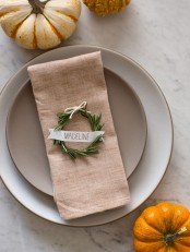 a rustic Thanksgiving table setting with neutral porcelain, mini pumpkins and a wreath with a card is great for Thanksgiving
