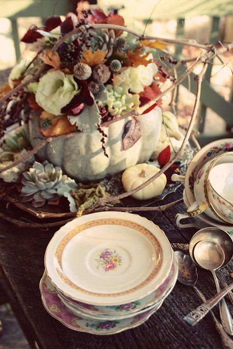 a vintage rustic Thanksgiving tablescape done with a farmhouse centerpiece - a pumpkin with blooms, leaves and berries and vintage porcelain and cutlery