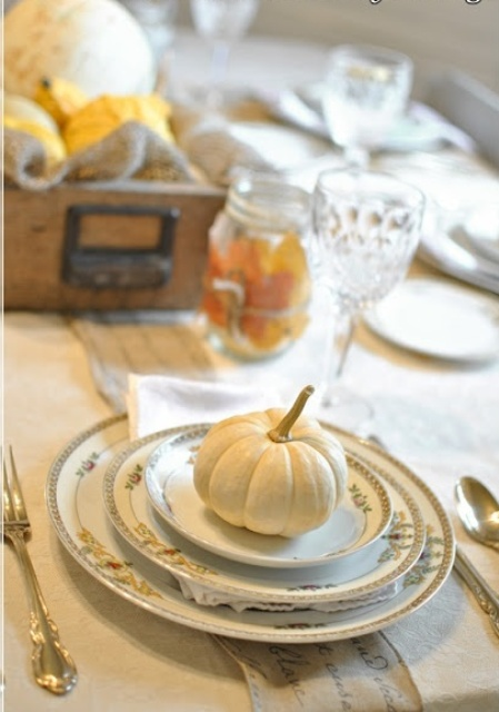 a refined vintage Thanksgiving tablescape with exquisite plates and saucepans with gold patterns, a crate with pumpkins and a leaf covered jar is very beautiful
