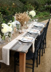 a rustic vintage Thanksgiving tablescape with a usual and burlap runner, a wheat and white bloom arrangements, white plates and neutral napkins, greenery and copper candleholders