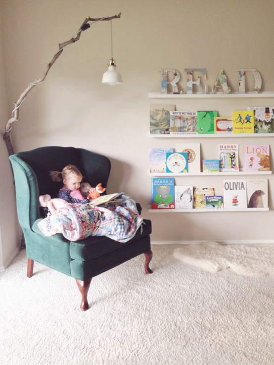 a cozy reading nook with a refined chair, ledges with books and a branch with a pendant IKEA Ranarp lamp is very cute
