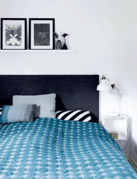 a monochromatic bedroom with white IKEA Ranarp lamps on nightstands and a gallery wall on a ledge