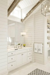 a neutral bathroom with wooden walls, wooden beams and a large vanity with a mirror