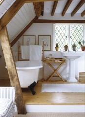 a modern farmhouse bathroom in white, with wooden beams on the walls and ceiling, a tub, vintage sinks