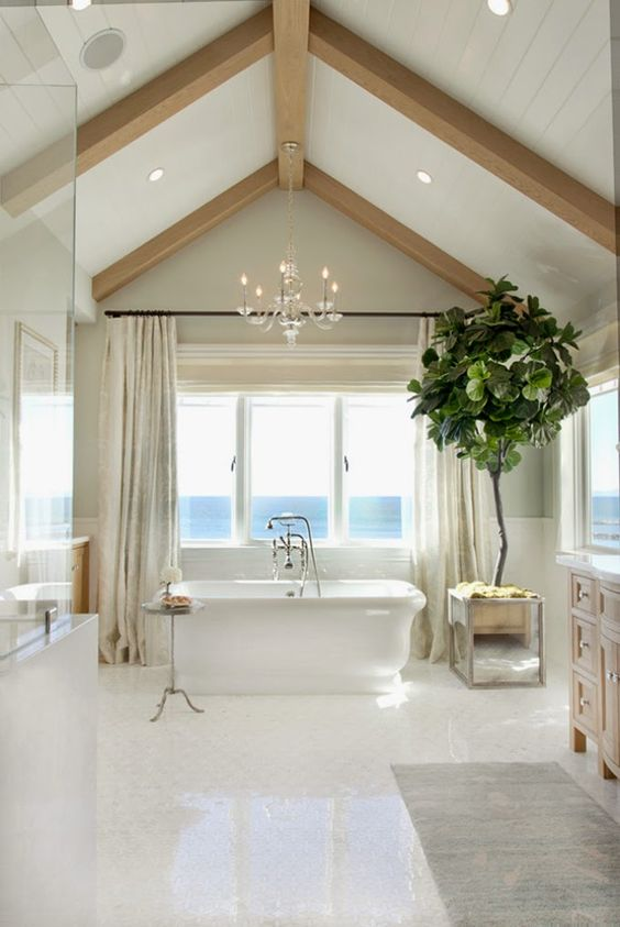 a seaside bathroom in neutrals, with wooden beams, built in lights, a tub, a shower space and windows for a view