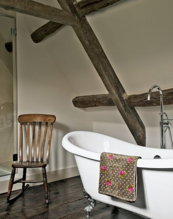 a modern farmhouse bathroom with neutral walls, a wooden floor and matching wooden beams plus a vintage bathtub