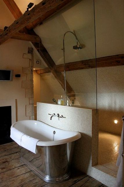 a modern farmhouse bathroom with neutral walls, a ceiling with wooden beams, a metal tub and modern fixtures