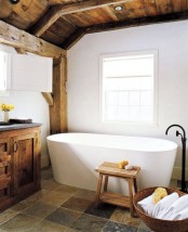 a modern farmhouse bathroom with white walls, a modern tub, a wooden ceiling with beams and a wooden vnaity