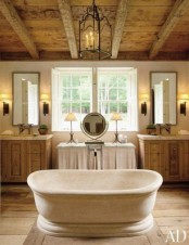 a farmhouse bathroom clad with wood, with a wooden ceiling and beams, two vanities and a vintage tub