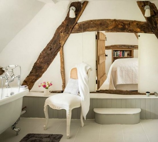 a vintage bathroom with grey paneling, wooden beams on the wall, a vintage tub and vintage fixtures