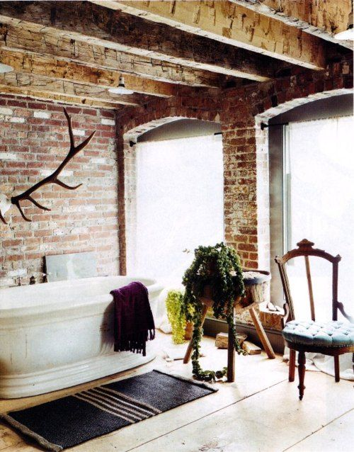 a vintage industrial bathroom with brick walls, wooden beams, a tub, vintage chairs and a striped rug
