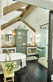 a farmhouse bathroom with a dark floor, wooden beams, a vintage tub and vintage furniture plus a shower space