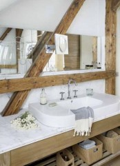 a farmhouse bathroom in white, with wooden beams and a wooden vanity, a white sink and a long mirror
