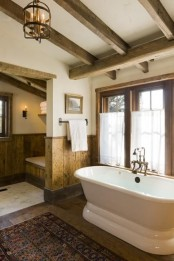 a rustic vintage bathroom with wooden beams, wood paneling on the walls, a boho rug and a tub