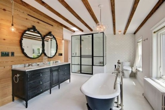 a farmhouse bathroom with wooden beams on the ceiling, a wooden accent wall, a shower clad with glass and a tub
