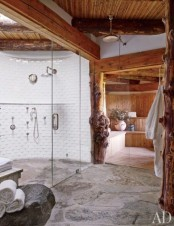 an eclectic bathroom with a stone floor, a shower clad with white tiles, a skylight, a sauna space and wooden beams on the ceiling