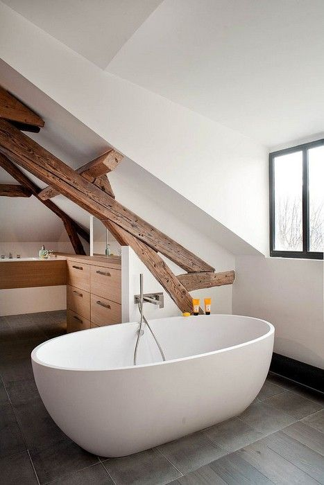 a modern farmhouse bathroom with white walls, wooden beams, a vanity and a free-standing tub by the window