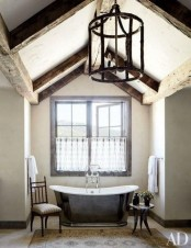 a vintage bathroom with dark wooden beams, a metal clad tub, refined chairs and a vintage chandelier