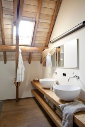 a modern farmhouse bathroom with a wooden ceiling, wooden beams, a floating vanity with sinks