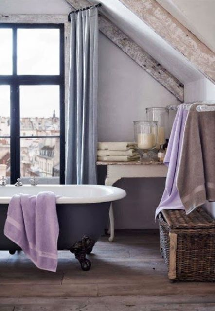 a vintage-inspired bathroom in neutrals and pastels, with a refined tub, lilac textiles, grey curtains and whitewashed wooden beams for a worn look