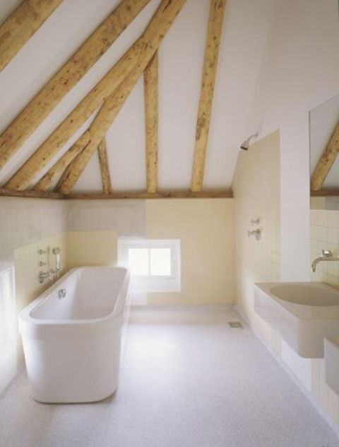 a neutral bathroom with a tile floor, warm colored walls, wooden beams and a free-standing tub