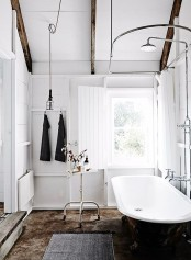 a Scandinavian bathroom with white walls, wooden beams, a black tub and metal fixtures