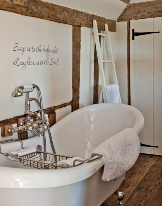 a refined vintage-inspired bathroom in white, with a wooden floor, wooden beams and a chic tub plus vintage fixtures