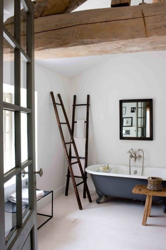 a vintage rustic bathroom with white walls, a grey tub, wooden beams and ladders plus a simple mirror in a wooden frame