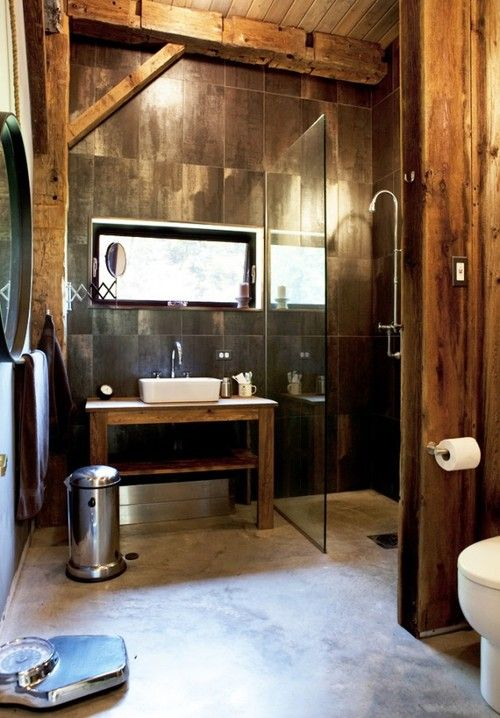 a rustic industrial bathroom clad with brown tiles and rough wood, with exposed wooden beams and a small window for a bit of light