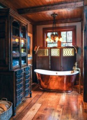 a rustic vintage bathroom with stained wood, with beams on the ceiling, with a large storage unit and a metal clad tub