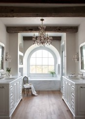 a refined bathroom with neutral walls, wooden beams on the ceiling, a refined crystal chandelier and white vanities
