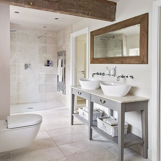 a modern rustic bathroom with neutral tiles, a vanity with two sinks, a wood frame mirror and wooden beams