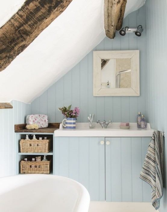 a blue bathroom with light blue walls, wooden beams, a tub and a vanity with a sink