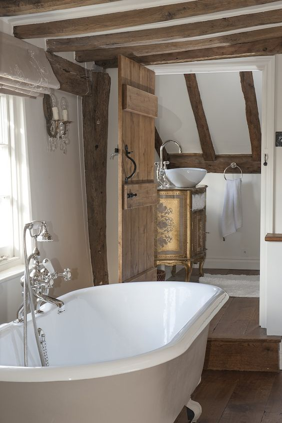 a rustic vintage bathroom with wooden beams on the walls and ceiling, a vintage tub and vintage furniture