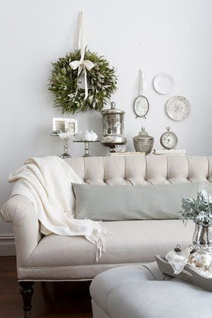 a fresh greenery wreath and a greenery arrangement on the table enliven the living room and make it fresh