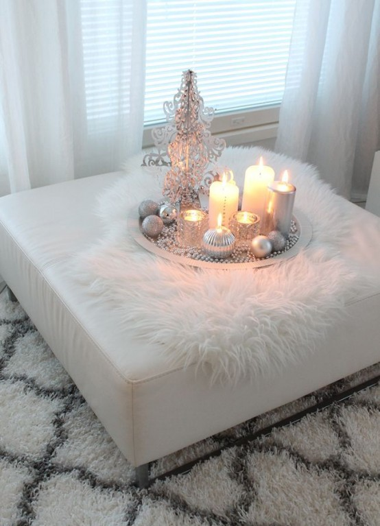a fluffy rug and a white faux fur throw on the ottoman make the living room more welcoming and cozy