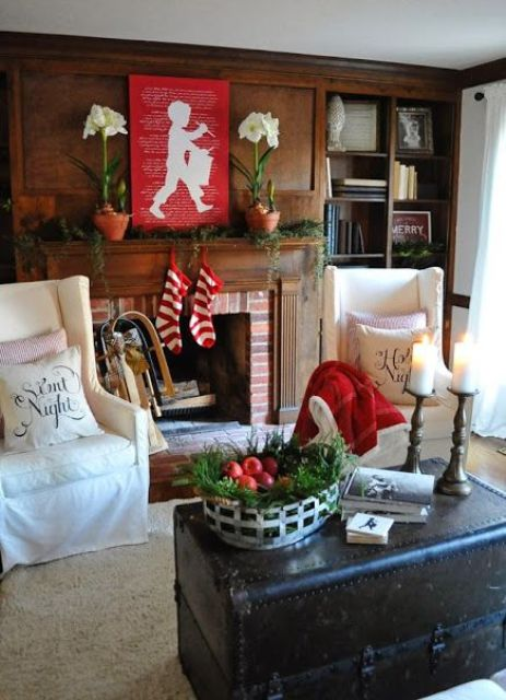 a living room spruced up with holiday reds, evergreens and white blooms to refresh it and make it feel festive