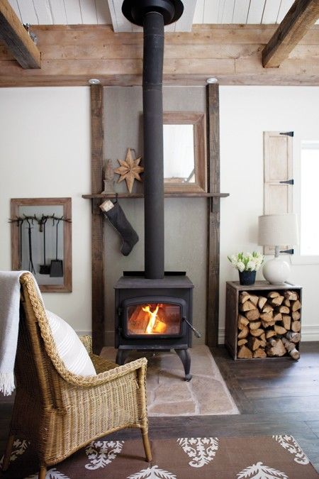 a vintage metal hearth and a firewood stand make up a very cozy and welcoming nook in the living room