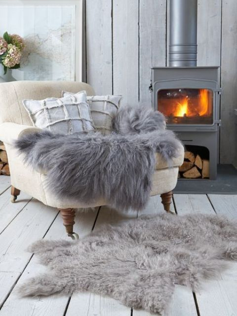 a vintage-inspired metal hearth with a chair by it and some faux fur is the greatest nook to spend some time