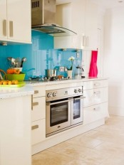 a white kitchen with a glossy blue backsplash and stainless steel appliances is a stylish space with a bold touch