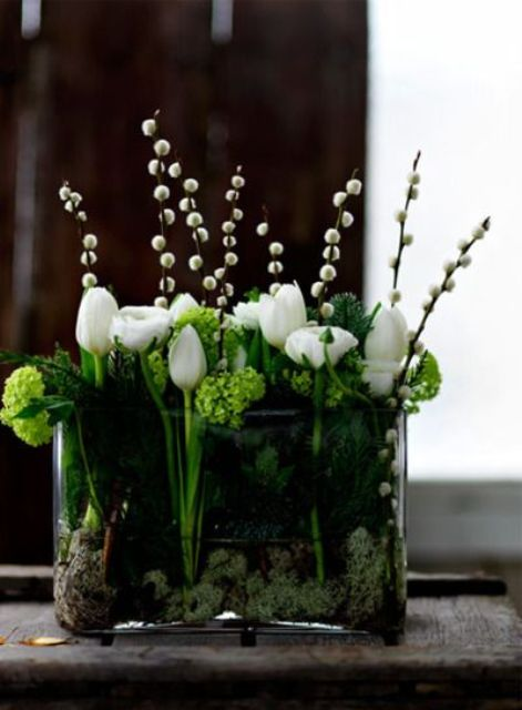 a clear glass vase with greenery, moss, white blooms and willow is a bright and catchy piece for every spring home