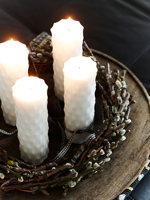 a Nordic spring home decoration of a wood slice, a willow wreath and some white candles for Easter