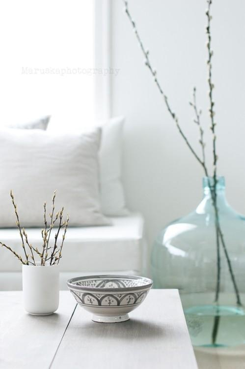 some willow in a mug and in a large glass bottle on the floor will make your living room feel like spring