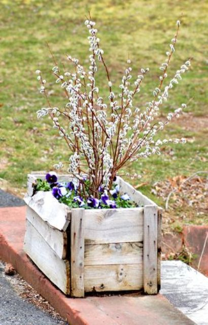 a wooden box with greenery, bright blooms and willow is a cool outdoor decoration for spring