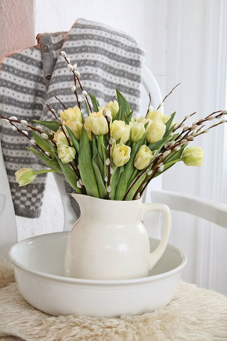 a white jug centerpiece with yellow tulips and willow is ideal for spring or Easter and brings a rustic feel